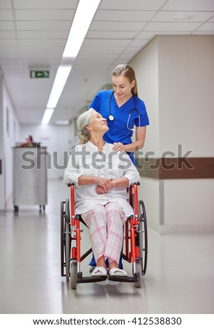 medicine, age, support, health care and people concept - happy nurse taking senior woman patient in wheelchair at hospital corridor - stock photo