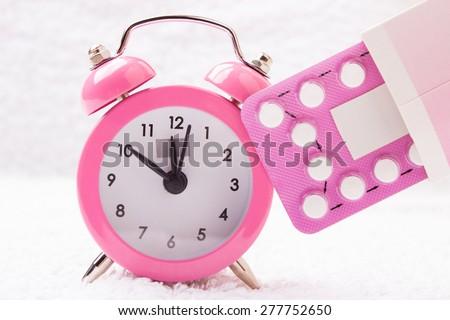 medicine and birth control. alarm clock and contraceptive pills - stock photo
