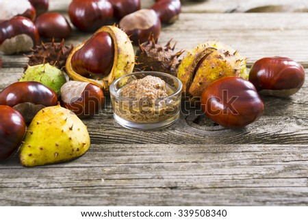 medicine and cosmetics raw ingredient: alcohol tincture from horse chestnuts on old wood table background - stock photo