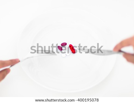 Medicine and Diet supplement concept. Person eating pills on a plate with a fork and knife. - stock photo