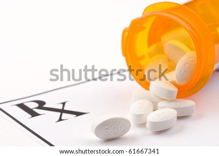 Medicine bottle and pills laying on prescription. - stock photo