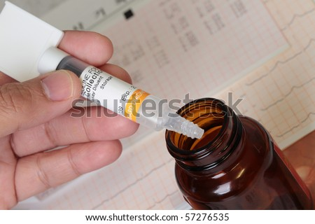 medicine bottle and spatula filler with medical result as background. - stock photo