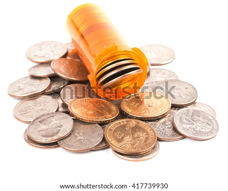 Medicine bottle filled with money, on top of a heap of quarters and dollar coins, concept of expensive medical care; on white - stock photo