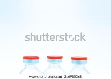 Medicine bottle for injection. Medical glass vial for vaccination. Science equipment, liquid drug or vaccine from treatment, flu in laboratory, hospital or pharmacy. Orange, yellow, red cover - stock photo