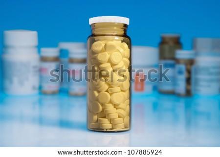 Medicine bottle on blue background - stock photo