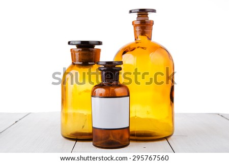 medicine bottles on wooden table isolated on white - stock photo