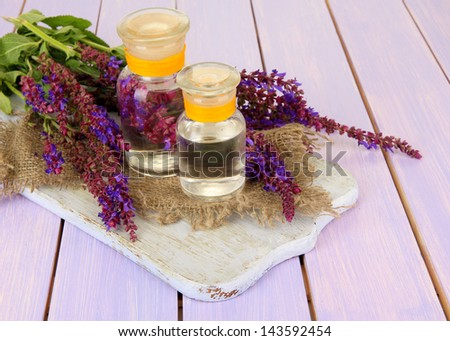 Medicine bottles with salvia flowers on purple wooden background