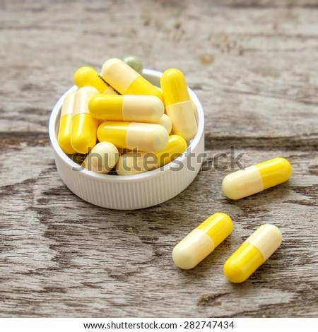 Medicine Capsules yellow on wooden - stock photo