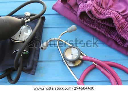 Medicine concept - stethoscope, doctor's uniform and blood pressure equipment  - stock photo