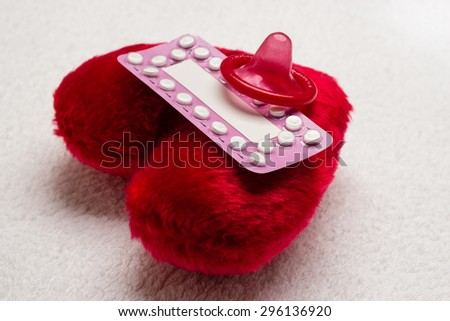 Medicine contraception love and birth control. Oral contraceptive pills condom on red heart shaped little pillow - stock photo
