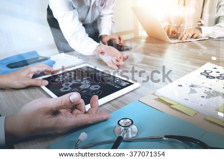 Medicine doctor hand working with modern computer and digital pro tablet with his team with graphics medical diagram on wooden desk,sun flare effect           - stock photo