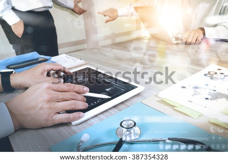 Medicine doctor hand working with modern computer and digital pro tablet with his team with digital medical diagram on wooden desk as medical concept