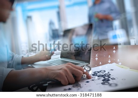 Medicine doctor hand working with modern computer and two colleagues discussing data  on wooden desk as medical concept  - stock photo