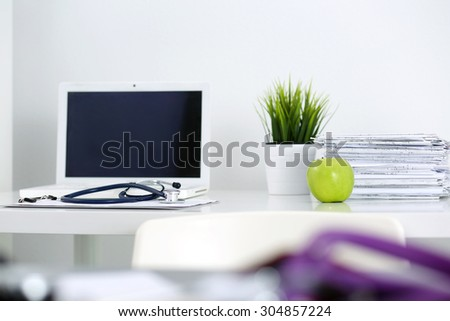 Medicine doctor's working table. Laptop, papers, green apple and stethoscope lying on table at physician's office. Healthcare and medical concept - stock photo