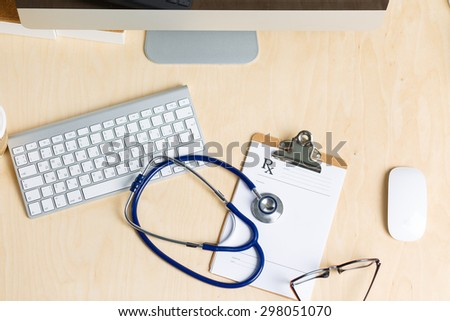 Medicine doctor's working table view from top. Monitor, keyboard, mouse, clipped pad with prescription list and stethoscope lying on table at physician's office. Medical concept - stock photo