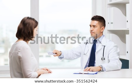 medicine, health care, medication and people concept - doctor with clipboard giving pills to young woman at hospital