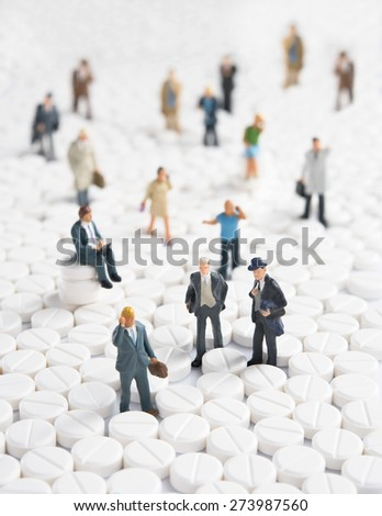 Medicine men. Close-up of figurines on the heap of pills - stock photo