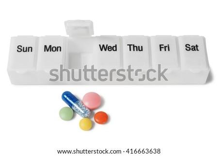 Medicine organizer and pills on white background - stock photo