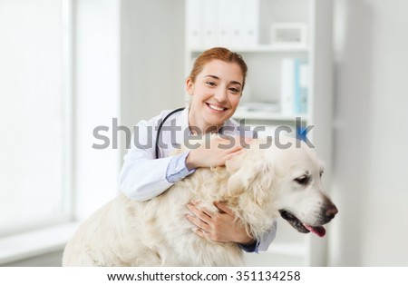 medicine, pet, animals, health care and people concept - happy veterinarian or doctor with golden retriever dog at vet clinic - stock photo