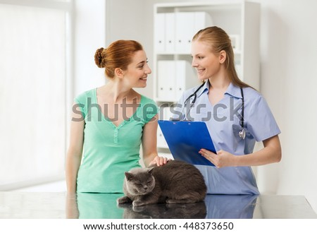 medicine, pet, animals, health care and people concept - happy woman with british cat and veterinarian doctor with clipboard talking at vet clinic - stock photo