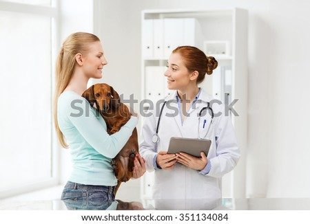 medicine, pet, health care, technology and people concept - happy woman holding dachshund dog and veterinarian doctor with tablet pc computer talking at vet clinic - stock photo