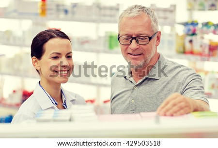 medicine, pharmaceutics, health care and people concept - happy pharmacist showing drug to senior man customer at drugstore - stock photo