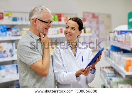 medicine, pharmaceutics, health care and people concept - happy pharmacist with tablet pc computer and senior man customer at drugstore - stock photo