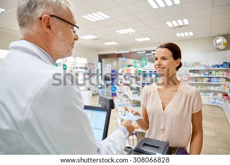 medicine, pharmaceutics, health care and people concept - smiling woman with wallet giving money to senior man pharmacist at drugstore cash register - stock photo