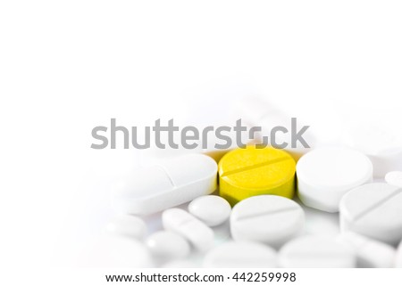 Medicine pills in various shapes, colors, and sizes on white background, selective focus with shallow depth of field on the yellow pill, room for copyspace on the top - stock photo