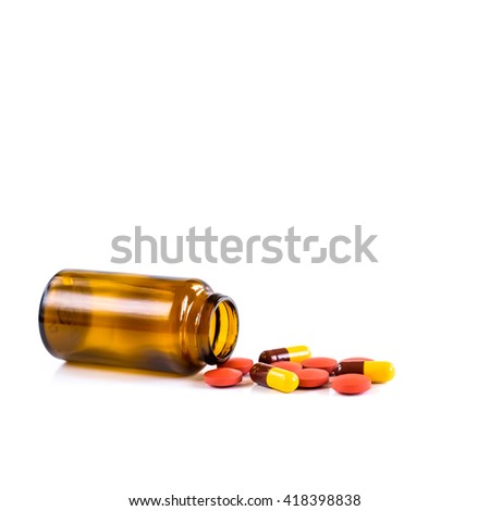 Medicine pills or capsules and bottle on white background. Drug prescription for treatment medication. Pharmaceutical medicament, cure in container for health. Antibiotic, painkiller closeup.