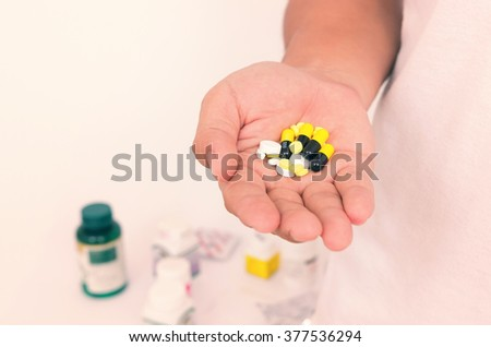 Medicine pills or capsules in hand, palm or fingers. Drug prescription for treatment medication. Pharmaceutical medicament, cure in container for health. vintage tone - stock photo