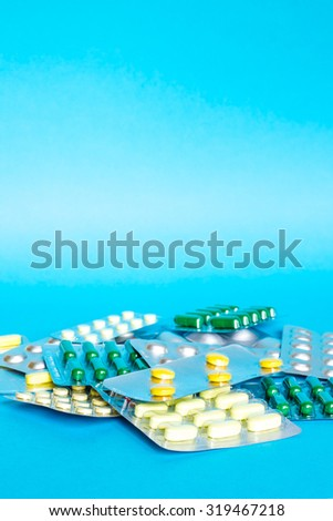 Medicine pills or capsules on blue background. Drug prescription for treatment medication. Pharmaceutical medicament, cure in container for health. Antibiotic, painkiller closeup. - stock photo