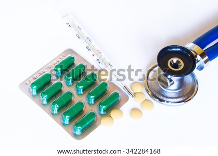 Medicine pills or capsules, stethoscope and thermometer on white background. Drug prescription for treatment medication. Pharmaceutical medicament, cure in container for health.  - stock photo
