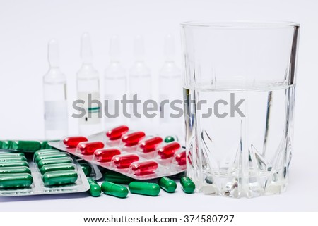 Medicine pills or capsules with glass of water and ampules on blue background. Drug prescription for treatment medication. Pharmaceutical medicament, cure in container for health.