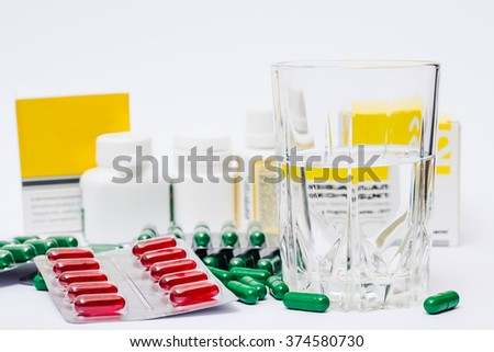 Medicine pills or capsules with glass of water and nose spray on white background. Drug prescription for treatment medication. Pharmaceutical medicament for flu, cold - stock photo