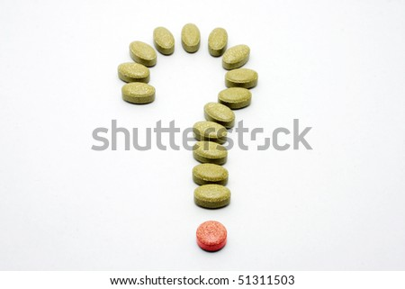 Medicine pills with question mark shape. - stock photo