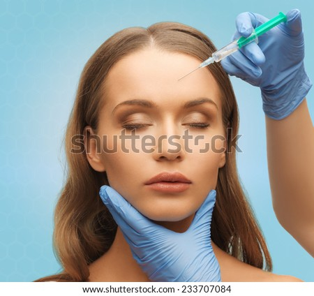 medicine, plastic surgery, beauty, health and people concept - hands in medical glove with syringe making injection to beautiful woman face over blue background - stock photo