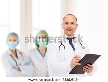 medicine, profession, teamwork and healthcare concept - smiling male doctor with clipboard and stethoscope writing prescription over group of medics - stock photo