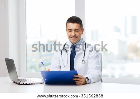 medicine, profession, technology and people concept - happy male doctor with clipboard and laptop computer in medical office - stock photo
