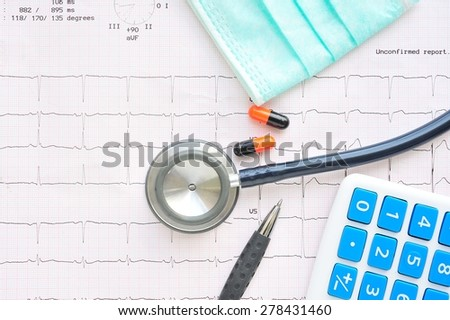 Medicine,Stethoscope and calculator on electrocardiogram paper.Health care costs. - stock photo