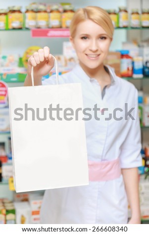 Medicine to keep healthy. Selective focus on a paper bag copyspace with a smiling druggist selective focus - stock photo
