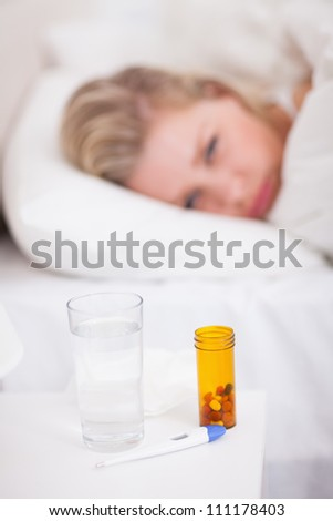 Medicines and thermometer on a beside table with a woman in her bed