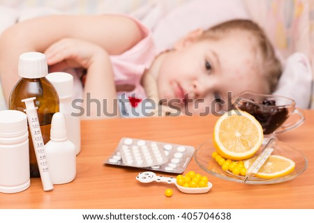 Medicines and vitamins on the table against the background of the child in bed suffering from chickenpox