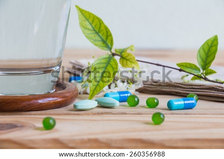Medicines and water on wooden table over wall grunge background - stock photo