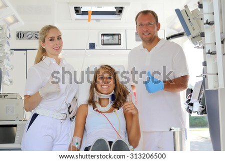 Medics with female patient in a Ambulance car happy with thumbs up - stock photo