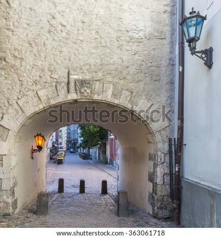 Medieval arch and street in old Riga city. Riga is the capital and largest city of Latvia, a major commercial, cultural, historical and financial center of the Baltic region - stock photo