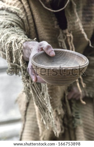 Medieval beggar holds out his wooden cup to ask for money - stock photo