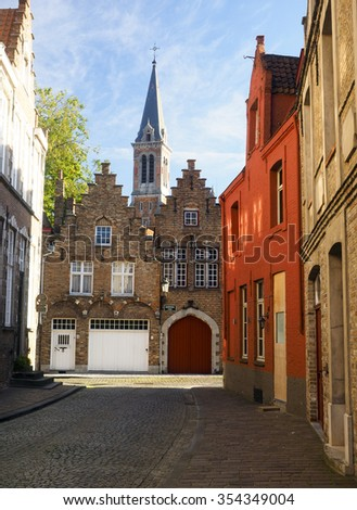 medieval buildings on cobblestone street with garage and cathedral in historic Brugge Bruges Belgium Europe - stock photo
