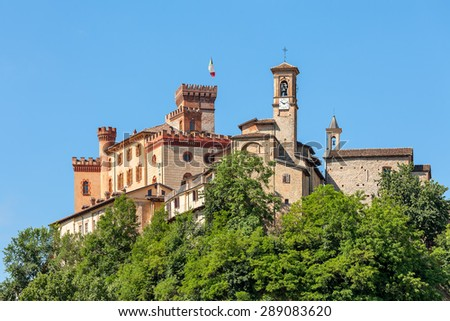 Medieval castle and church under blue sky in Barolo - small town in Piedmont, Northern Italy. - stock photo