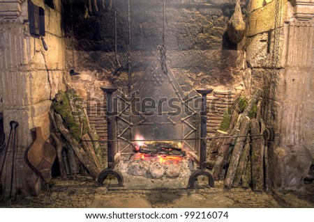 Medieval castle kitchen Stone fireplace with antique equipment - stock photo